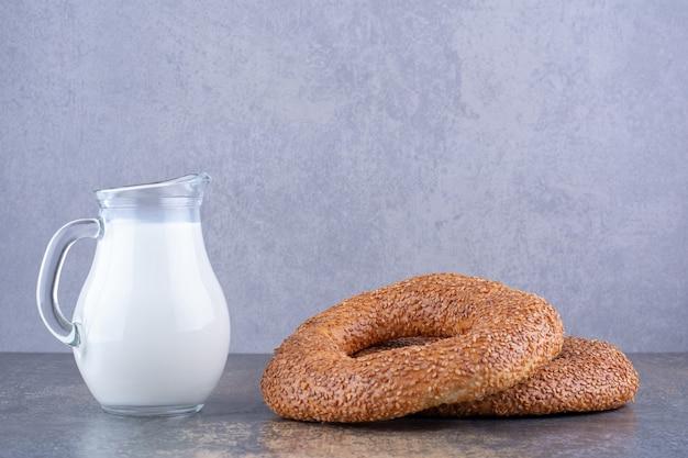 Bagels de gergelim com um pote de leite à parte