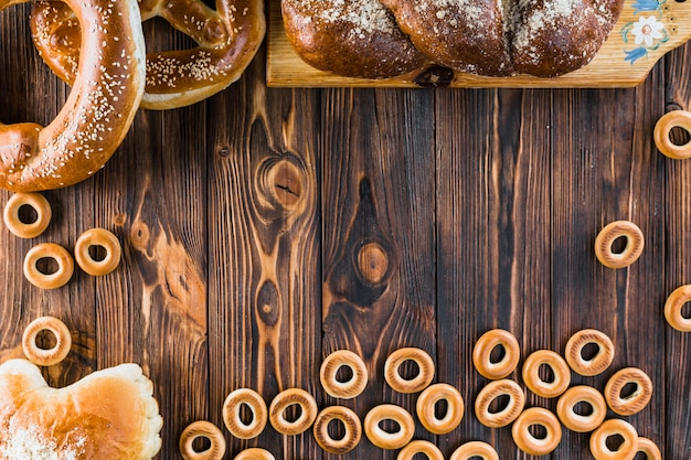 Bagels, pão trançado e pretzels na mesa de madeira