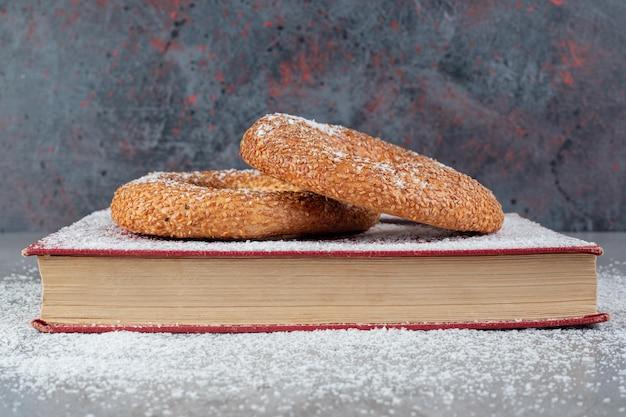 Bagels revestidos de gergelim em uma bandeja coberta com pó de coco na mesa de mármoreq.