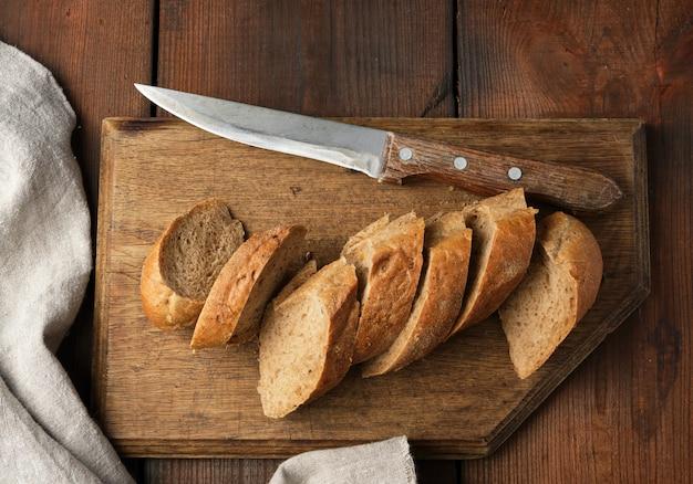 Baguete de farinha de centeio em fatias sobre uma tábua de madeira