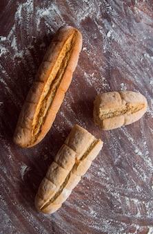 Baguete de trigo integral na vista superior de mesa de madeira