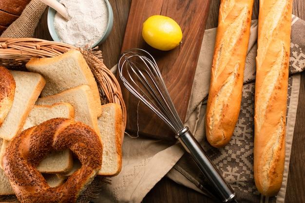 Baguete e bagels na cesta com limão e farinha