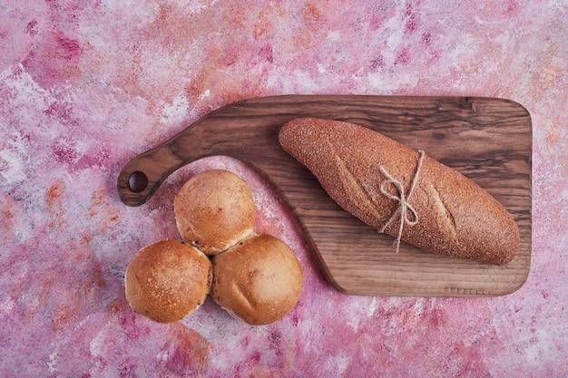 Baguete e pães em uma placa de madeira.