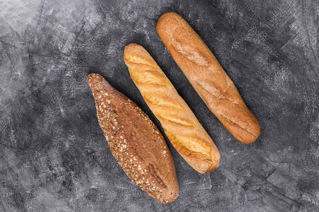 Baguete e pão no pano de fundo resistido