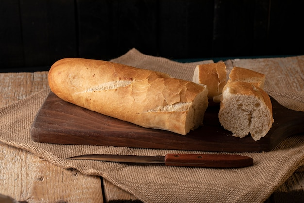 Baguete francesa cortada em uma placa de madeira