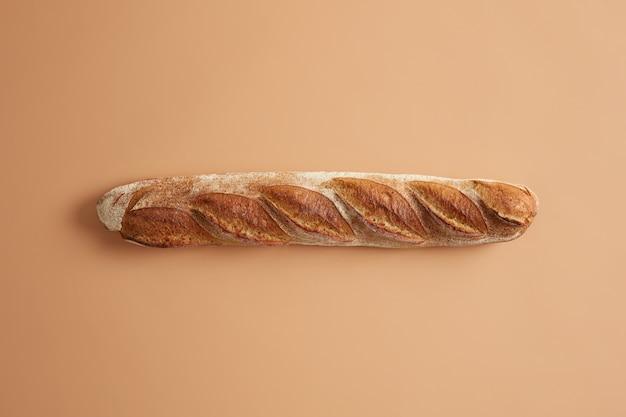 Baguete francesa longa com crosta dourada crocante isolada no fundo bege do estúdio. pão acabado de cozer para uma nutrição saborosa. tiro aéreo. saboroso produto gourmet assado na padaria. conceito de comida