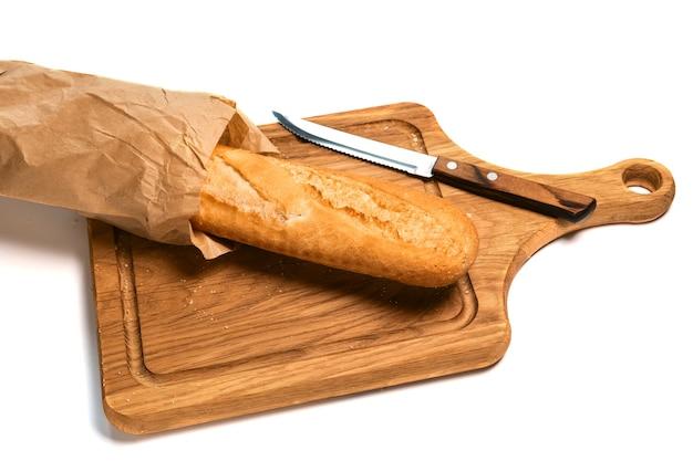 Baguete fresca parcialmente fatiada e faca de pão isolada na superfície branca