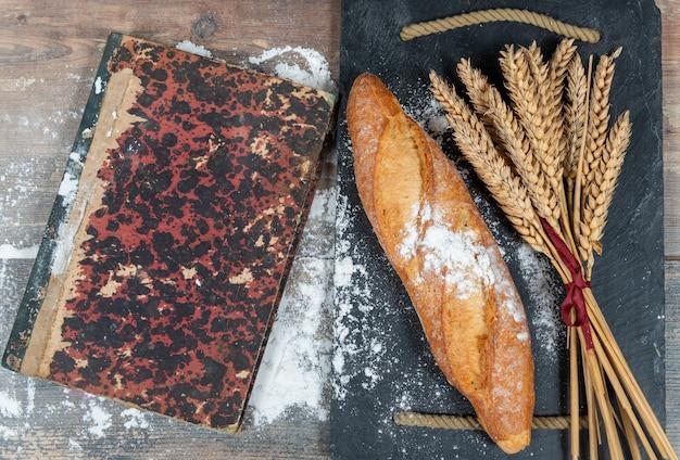 Baguete ou pão francês e algumas espigas de trigo