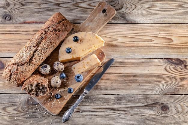 Baguete, queijo com especiarias e ervas, ovos de codorna, mirtilos.