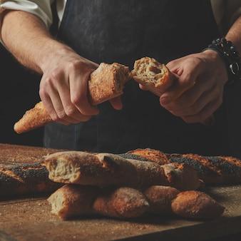 Baguete quente e fresca corte as fatias. rasgue um pedaço com as mãos dos homens