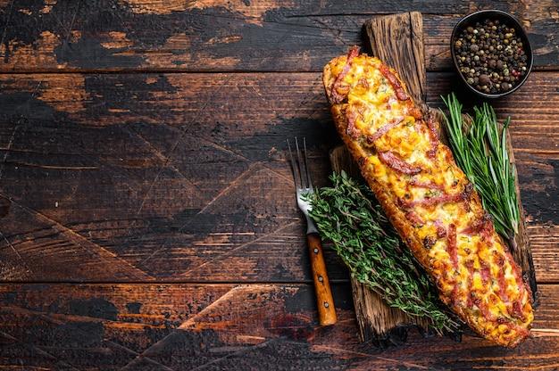 Baguete recheada com presunto, bacon, legumes e queijo na tábua de madeira. fundo de madeira escuro. vista do topo. copie o espaço.