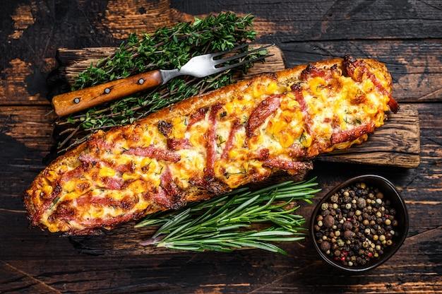 Baguete recheada com presunto, bacon, legumes e queijo na tábua de madeira. fundo de madeira escuro. vista do topo.