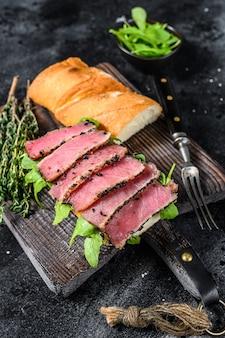 Baguete sanduíche de bife de atum com rúcula em uma placa de corte. fundo preto. vista do topo.