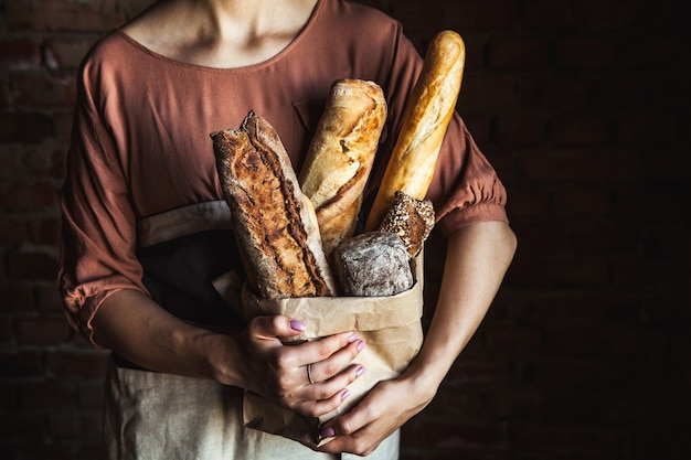 Baguetes francesas nas mãos femininas em um negro. cozimento caseiro