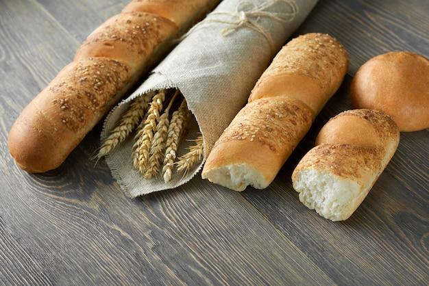 Baguetes franceses frescos deliciosos e painços envolvidos no papel do ofício na receita natural orgânica do retalho de madeira do mercado do alimento do supermercado da loja da loja do copyspace do worktop que come o conceito natural.