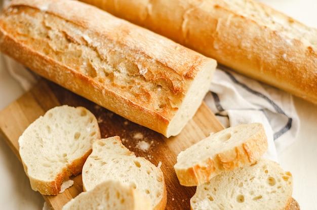 Baguetes frescos com uma crosta crocante picada em uma placa de corte