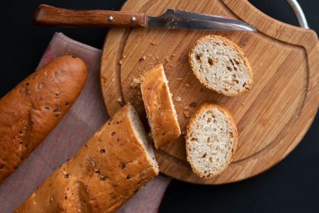 Baguette francesa cortada em uma placa de madeira, faca de pão que coloca ao redor