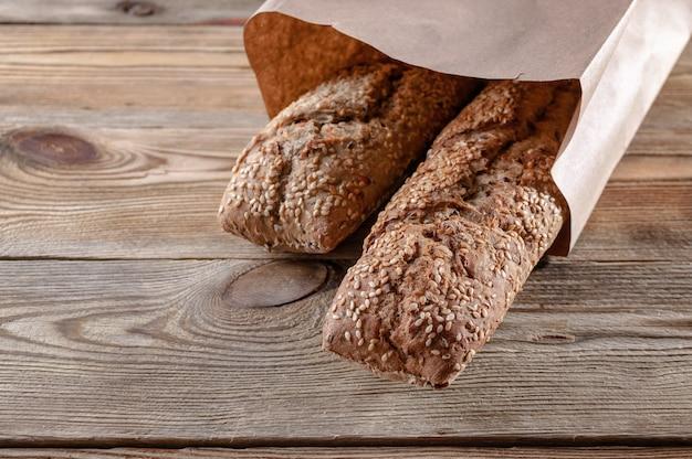Baguettes apetitosos com sementes e porcas de sésamo em um saco de papel em um fundo de madeira. conceito de comida saudável