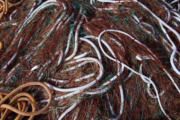 Bagunça de padrão de redes de pesca empilhados no porto