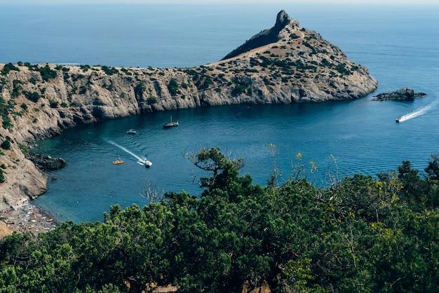 Baía azul de cape kapchik com barcos e um navio na crimeia