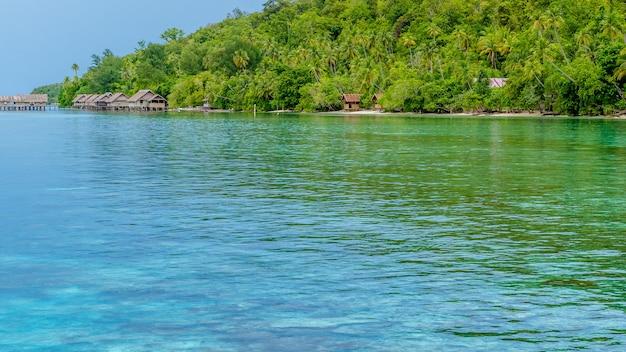 Baía com corais subaquáticos em frente à estação de mergulho e hospedarias na ilha kri, raja ampat, indonésia, papua ocidental.