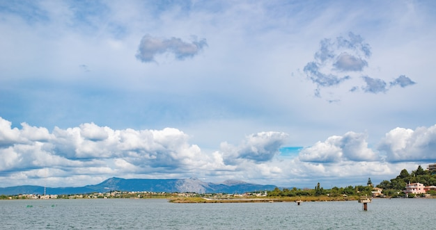 Baía de areia verde incrível com águas cristalinas, grandes pedras na ilha de corfu, grécia. bela paisagem da praia do mar jônico. tempo ensolarado, céu azul.