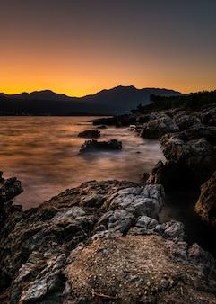 Baía de kotor com montanhas ao longe ao pôr do sol em montenegro