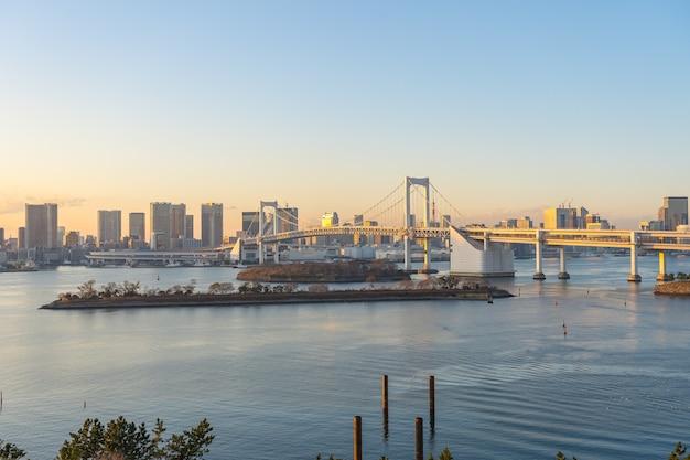 Baía de tóquio ao pôr do sol com vista da ponte do arco-íris na cidade de tóquio, japão.