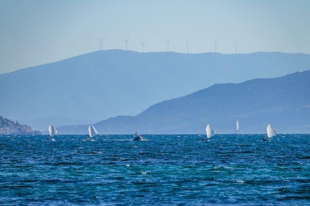 Baía de verão em um dia ensolarado. costas montanhosas. vários pequenos iates esportivos e um ônibus em um barco a motor