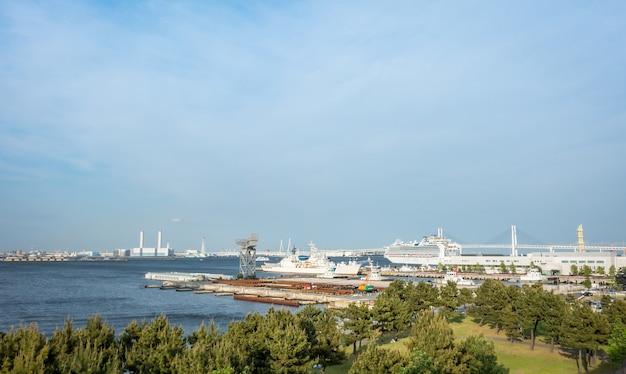 Baía de yokohama com navio de guerra e navio de passageiros.