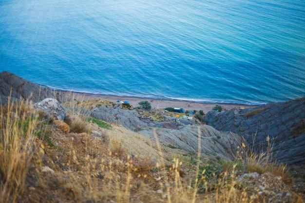 Baía do mar selvagem com pessoas e tendas