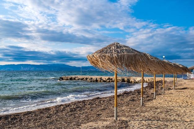 Baía incrível com águas cristalinas na ilha de corfu, grécia. bela paisagem da praia do mar jônico com guarda-sóis de palha, dia ensolarado.