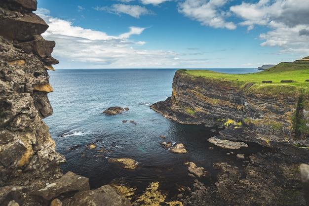 Baía irlandesa cercada pelas colinas cobertas de verde.
