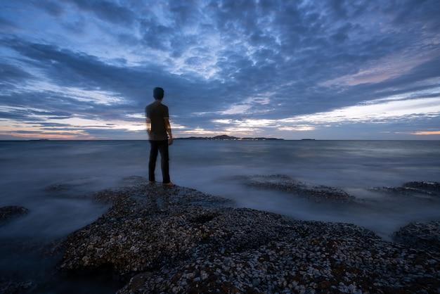 Baía rochosa tranquilo com uma parte traseira do homem após o pôr do sol.