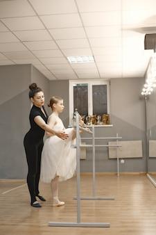 Bailarina bonitinha em traje de balé branco. jovem está dançando na sala. menina na aula de dança com o professor.