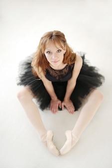 Bailarina clássica mulher de vestido preto praticando para o cisne negro
