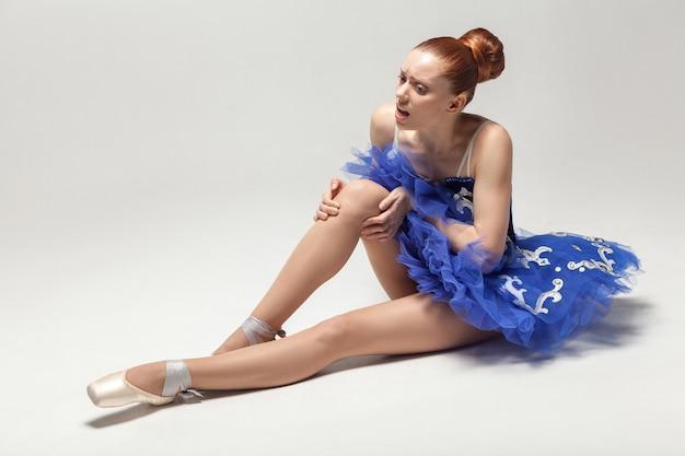 Bailarina com dor no joelho segurando o joelho machucado enquanto está sentada no chão branco
