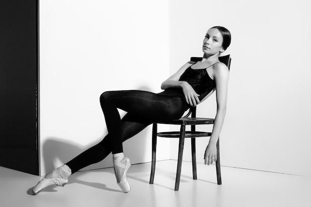 Bailarina com roupa preta, posando em uma cadeira de madeira, fundo de estúdio.