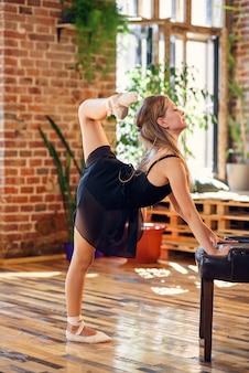 Bailarina com tutu preto, fazendo exercícios de alongamento e aquecimento.