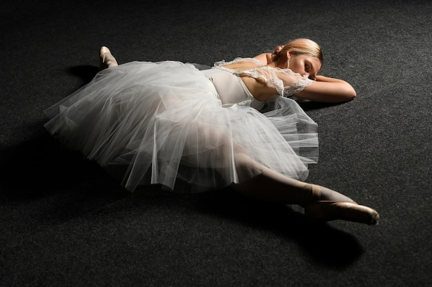 Bailarina com vestido tutu, fazendo uma divisão no chão