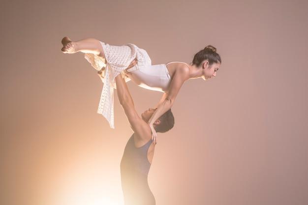 Bailarina da vista lateral que está sendo sustentada