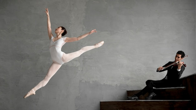 Bailarina dançando a música tocada pelo violinista