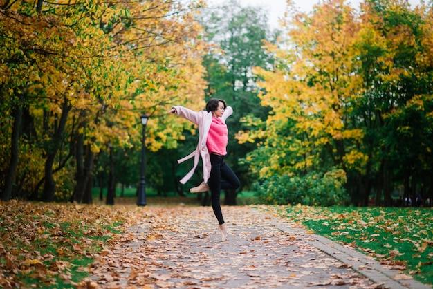 Bailarina dançando com sapatilhas de ponta no parque dourado do outono, em pose de balé nas folhas amarelas