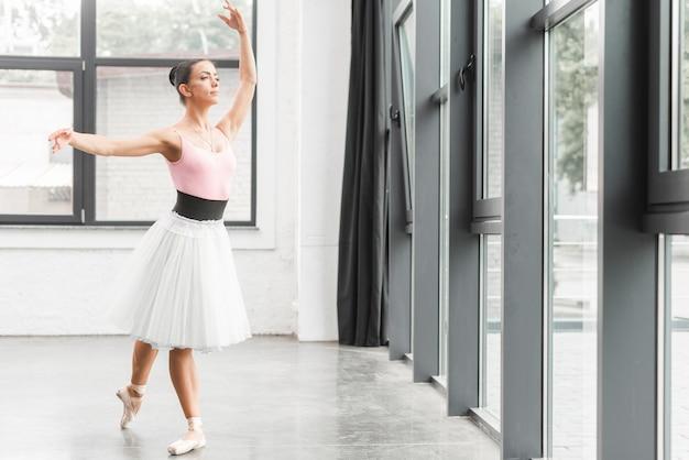 Bailarina dançando na bela sala de ensaio