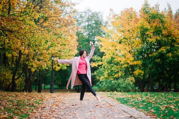 Bailarina dançando na natureza entre folhas de outono com casaco claro.