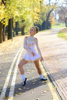 Bailarina dançando no parque natural entre as folhas de outono.