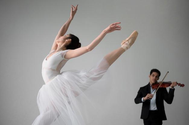 Bailarina dançando no vestido tutu e músico tocando violino