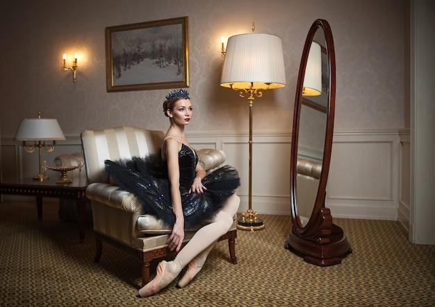 Bailarina de tutu preto sentada em uma poltrona em um interior luxuoso