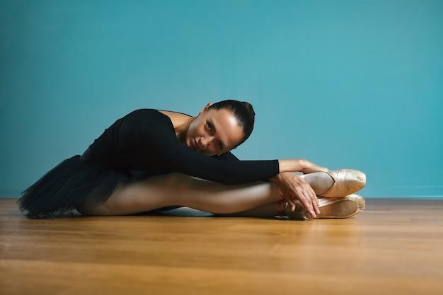 Bailarina de uma linda mulher em tutu e ponta em maiô preto, posando no estúdio sobre fundo azul.