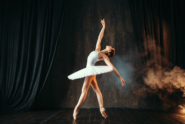 Bailarina de vestido branco dançando na aula de balé